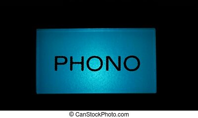 Phono button blue color on black background of radio...