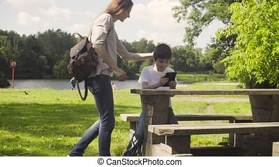 Boy playing a tablet in a park.