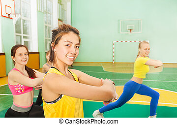 Happy Asian teenage girl warming-up in sports hall -...