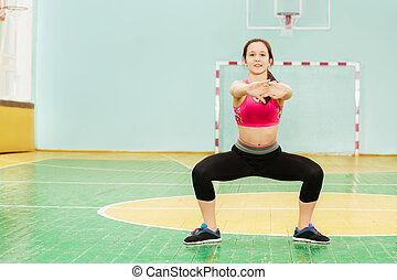 Active girl performing sumo squat in sports hall - Portrait...