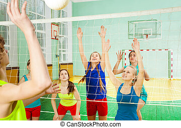 Teenage boys and girls playing volleyball game