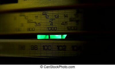 Panel of retro radio receiver illuminated by lights and...