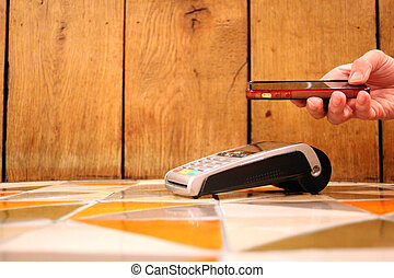 contactless payment phone pdq with hand holding credit card...