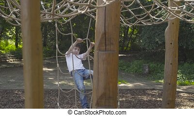 A boy climbing on a playground equipment in the park