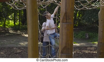 A boy climbing on a playground equipment. Mom watching for...