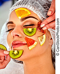 Facial mask from fresh fruits for woman. Beautician apply...