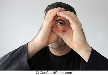 Peeping man - Man pretends to peek through a hole with his...