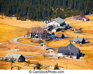Mountain village Jizerka in Jizera Mountains in Northern Bohemia, Czech Republic. Simple huts around mountain brook on sunny spring day with yellow grass and rest of snow fields