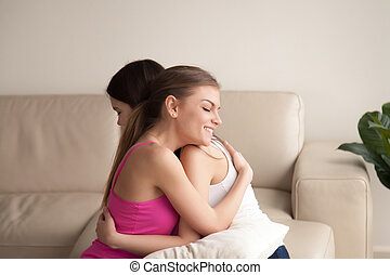 Two young women friends hugging on sofa