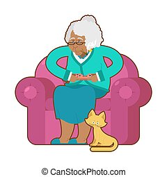 African American grandmother and joystick. Black granny play video games. old woman on an armchair with gamepad. Cat and elderly woman