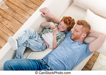 High angle view of happy father and son lying together on sofa at home, family fun at home concept