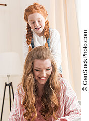 Beautiful happy mother and daughter having fun together at home, family fun at home concept