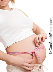 pregnant woman measures her belly