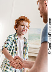 side view of father and smiling son shaking hands