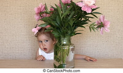 Funny baby with a vase of peonies flower at a birthday party.