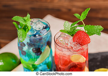 Top view of two bright alcoholic cocktails with mint, lime, ice, strawberries on the wooden background. Summer beverages.