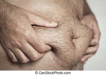 man grabbing the fat of his stomach