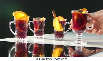 People take from the table glasses with mulled wine and...