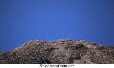peak of the volcano. From the volcano comes smoke - From the...