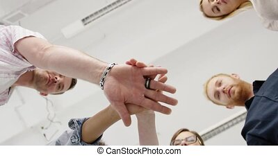 Coworkers stacking hands from below - From below shot in...