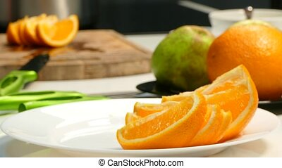 Hands lay an orange on a plate