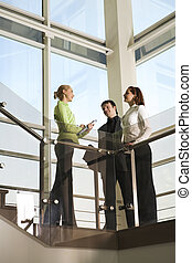 Team in the business building - Two girls and man are...