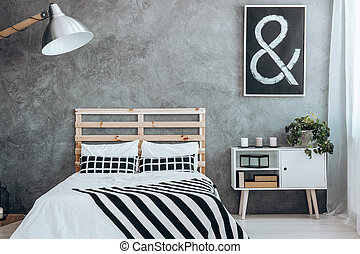 Coverlet and two pillows in stripes on king-size bed in grey...