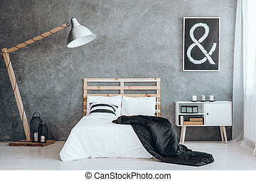 Black coverlet on king-size bed between design lamp and...