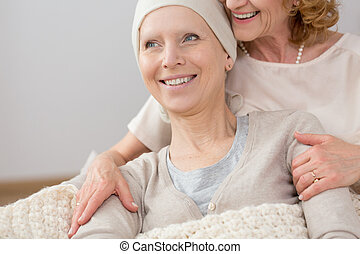 Woman supported by friend - Sick woman with scarf supported...