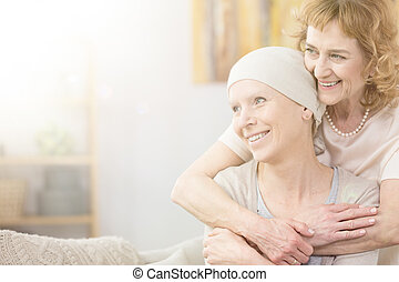 Supportive older woman hugging her friend struggling with...