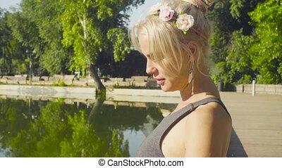 Portrait of young woman sitting near the lake and talking