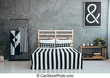 Stripped coverlet on wooden bed between hanger with dresses...