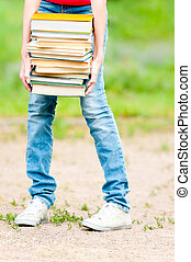 student girl holding big pile of heavy books