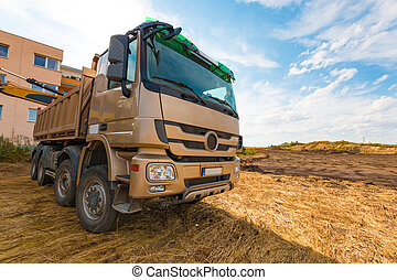 Yellow truck on the territory of beginning construction,...