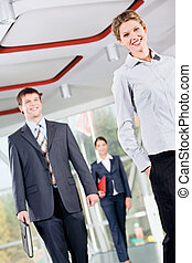Business people - Confident woman is walking in front of...