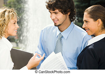 Positive conversation - Group of three people talking about...