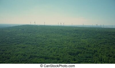 Aerial time lapse of wind genertors in forest area. Green...