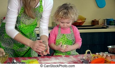 Beautiful woman and her adorable daughter kneading dough....