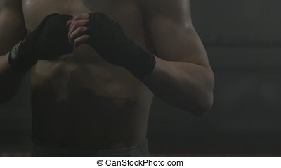 Boxer punching. Strong muscular boxer shadow boxing. Kickbox...