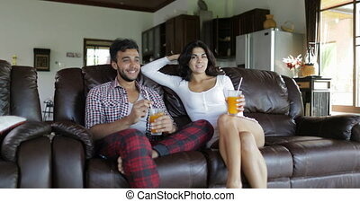 Couple Sitting On Coach In Living Room Drink Orange Juice,...