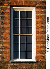 Close-up of white window in red Tudor building brick wall