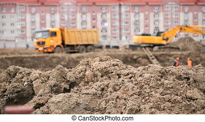 Excavator loads clay using bucket into dump truck