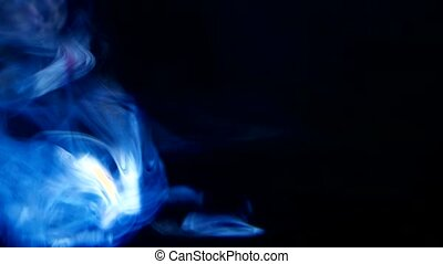 Closeup on black background, smoke and blue light from...