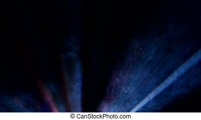 Moving multicolored beams of searchlights in nightclub smoke scene, closeup