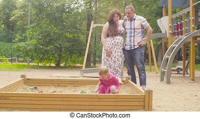 Little baby girl playing in sandbox on playground. Her...