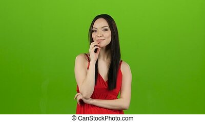 Girl is posing in front of the cameras, winking. Green screen