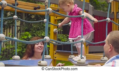 Little baby girl walking on a rope playground. Her parents...