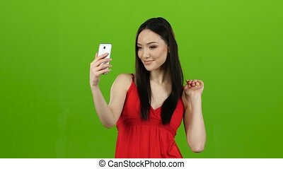 Asian girl does selfie, she smiles while looking at the...