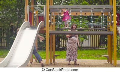 Little baby girl moving down the hill on playground. Her...