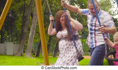 Man swinging his daughter and his wife on a swing